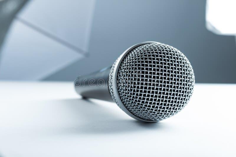 Een draadloze microfoon die op een witte lijst liggen Tegen de achtergrond van studiomateriaal, zachte dozen stock afbeelding