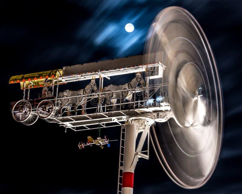 Een draaimolen spint voor een volle maan stock afbeeldingen