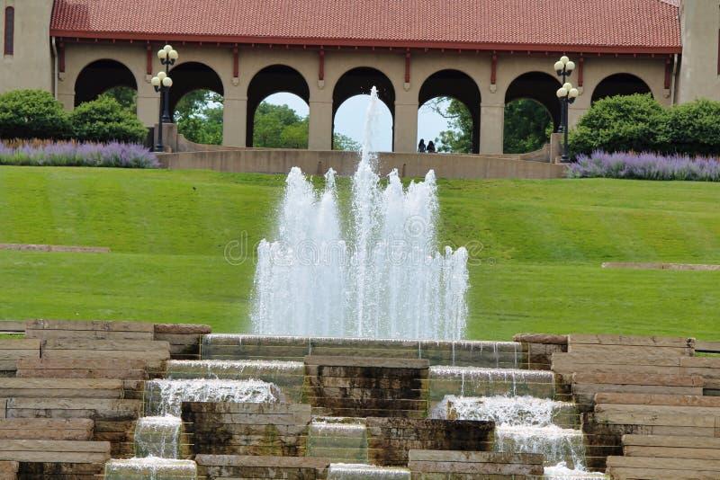 Een draperende fontein met torens van water die een paviljoen overzien stock foto