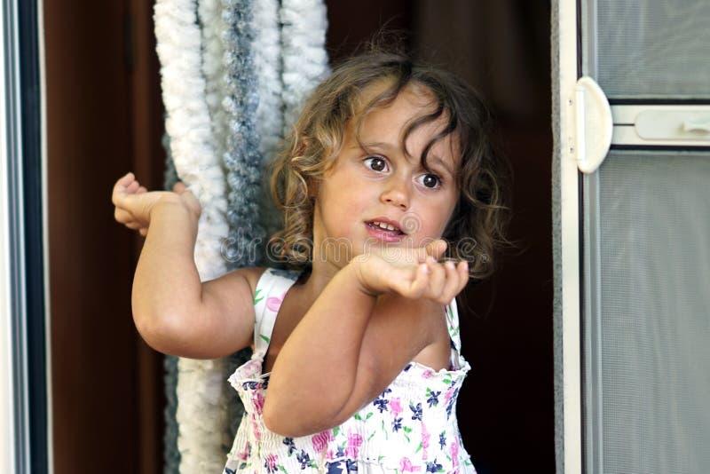 Een drie-jaar-oude blonde meisjesgebaren met haar handen royalty-vrije stock foto