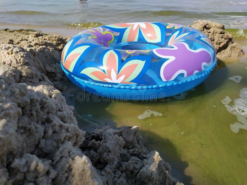 Een drijvende cirkel voor kinderen ligt op zandige riverbank dichtbij het water royalty-vrije stock afbeeldingen