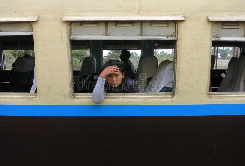 Een droevig en vermoeid Birmaans meisje die uit het venster van een oude trein kijken royalty-vrije stock foto's