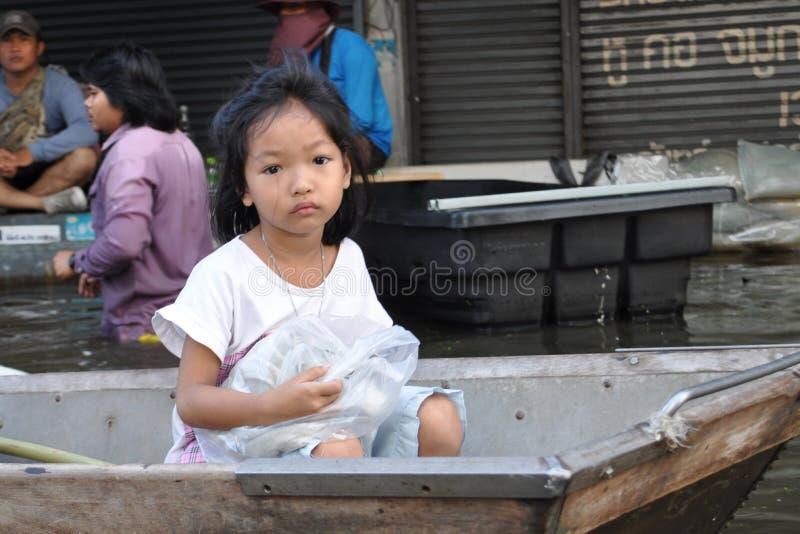 Een droevig ligglemeisje is op een boot, bekijkend de camera in een overstroomde straat van Bangkok, Thailand, op 06 November 201 royalty-vrije stock fotografie