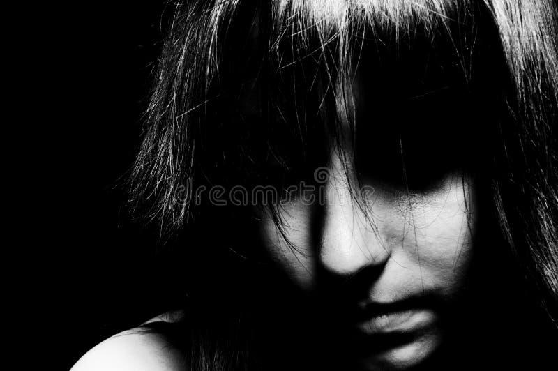 Een droevig meisje dat neer kijkt stock afbeelding
