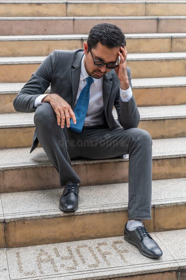 Een droevige het kijken jonge zakenmanzitting bij de trap royalty-vrije stock fotografie