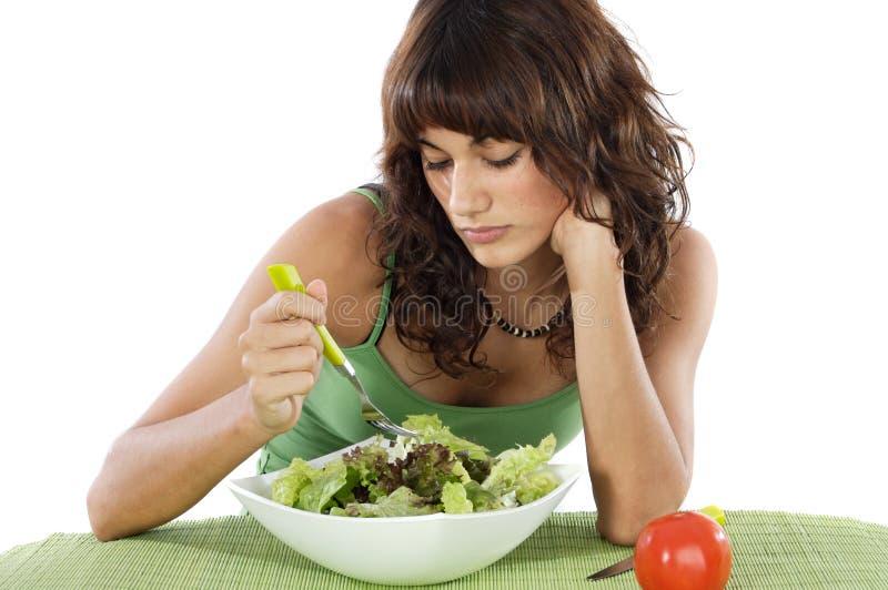 Een droevige tiener die salade eet