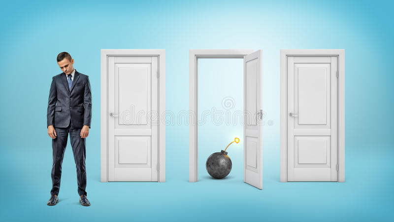 Een droevige zakenman met zijn hoofd verminderde tribunes dichtbij drie deuren waar men open is en een aangestoken bom toont stock fotografie