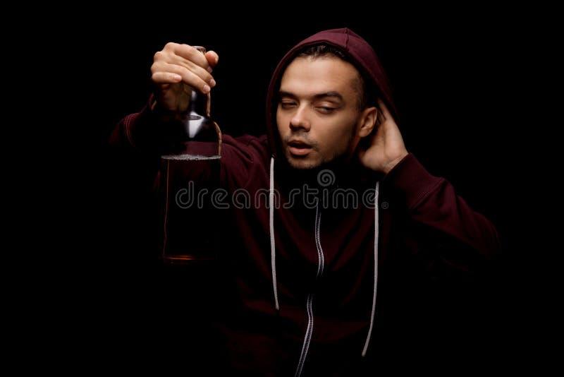 Een dronken kerel met een fles bier Jonge alcoholisch in een rode hoodie op een zwarte achtergrond Alcoholisch verslavingsconcept royalty-vrije stock foto