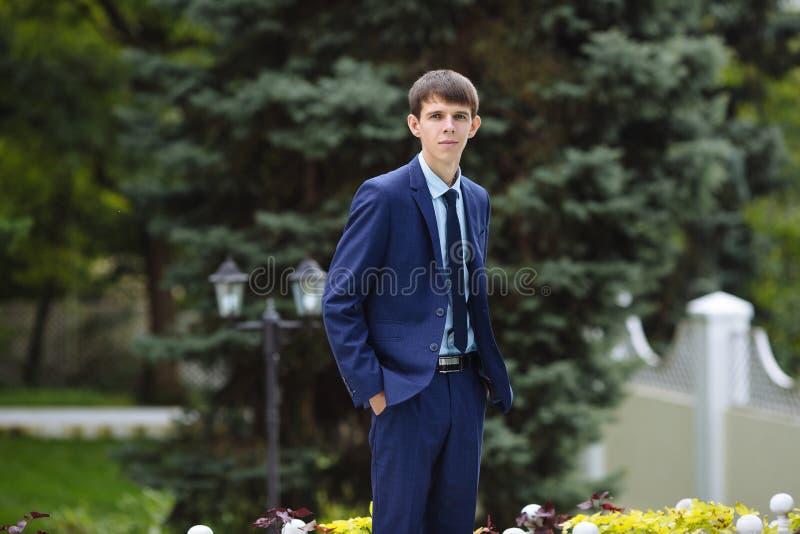 Een dunne lange kerel met het plakken van oren loopt in het park, gekleed in een klassiek blauw kostuum, houdt van hem indient zi royalty-vrije stock afbeelding