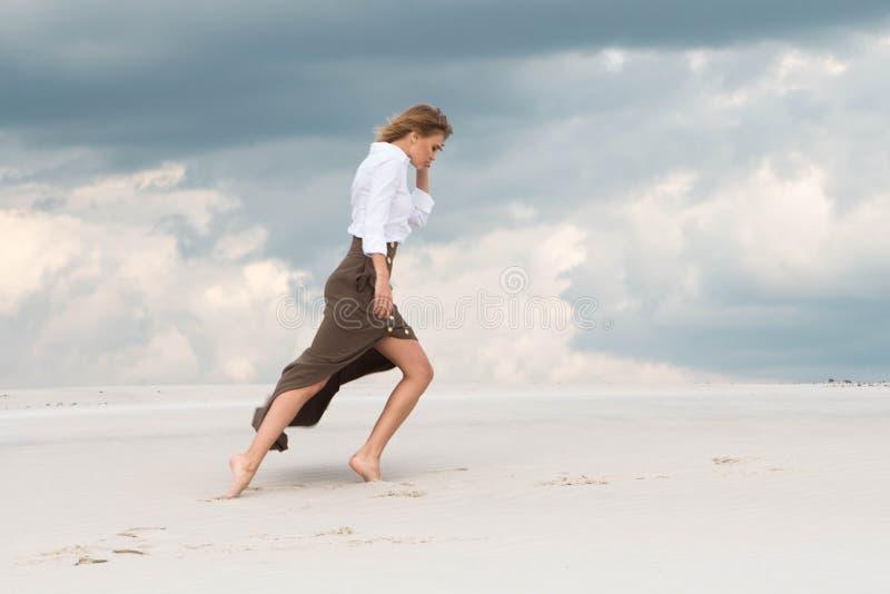 Een dunne meisjesgangen die zwaar de sterke wind overwinnen stock afbeelding