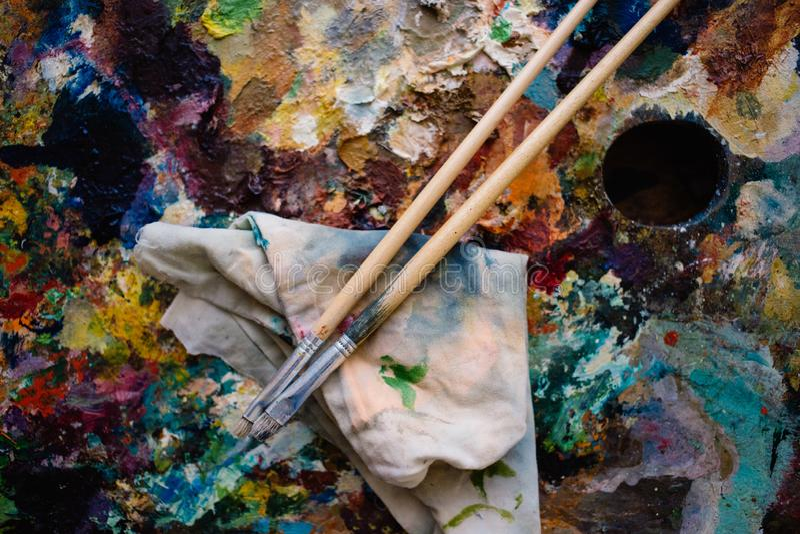 een echte artist& x27; s palet, olieverven en twee verfborstels stock afbeeldingen