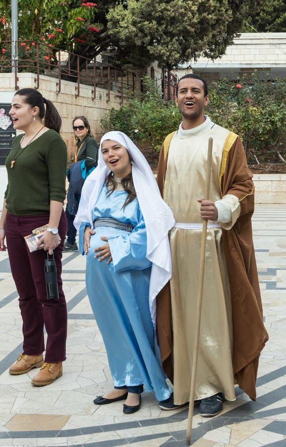 Een echtpaar - de echtgenoot en de zwangere vrouw in de kleren van de tijd van Jesus ` zingen een lied alvorens de Basiliek van A stock fotografie