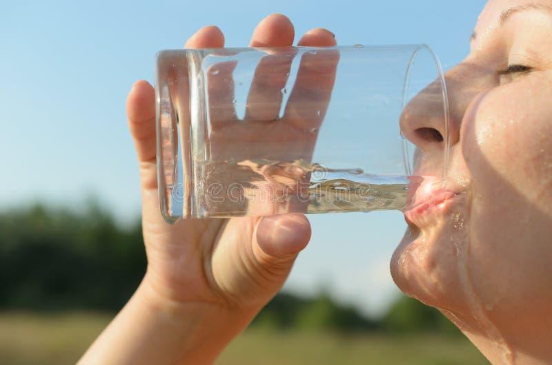 Een eenvoudige Europese jonge vrouw is drinkwater van een glasbeker tegen een blauwe hemel stock afbeelding