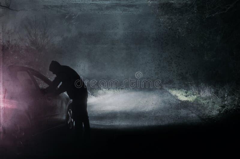 Een eenzaam cijfer die met een kap een auto onderzoeken Gesilhouetteerd op een de griezelige, mistige wintersweg van het land bij vector illustratie