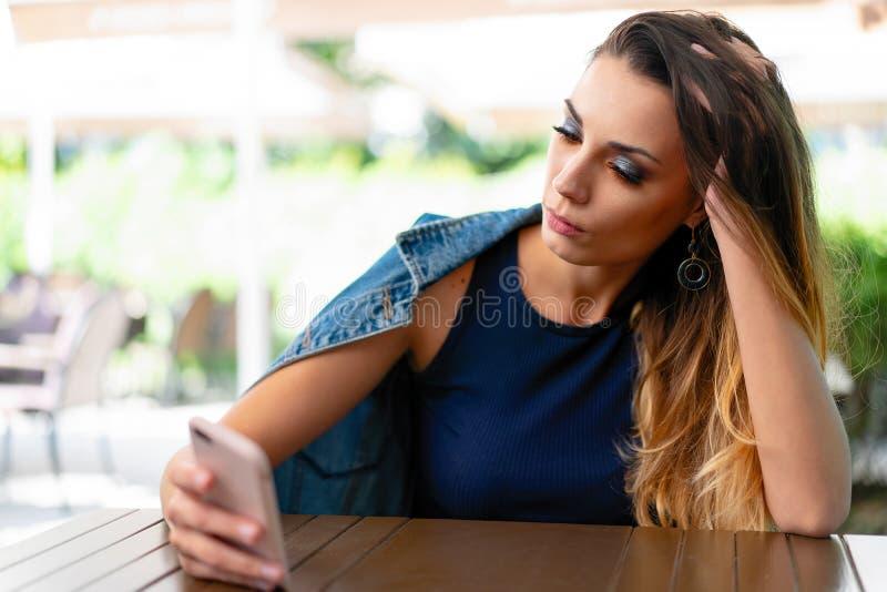 Een eenzaam droevig Kaukasisch meisje zit in een open de zomerkoffie met een telefoon in haar handen en is alleen droevig royalty-vrije stock foto