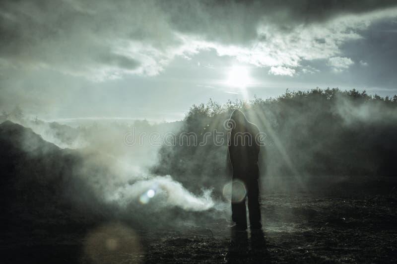 Een eenzaam gesilhouetteerd cijfer die met een kap zich buiten bevinden In een gebrand rokend landschap Met een hoog contrast gee stock afbeelding
