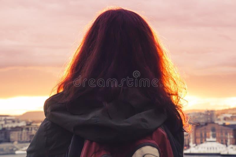 Een eenzaam meisje met een rugzak bevindt zich met achter haar en bekijkt bij stock foto's