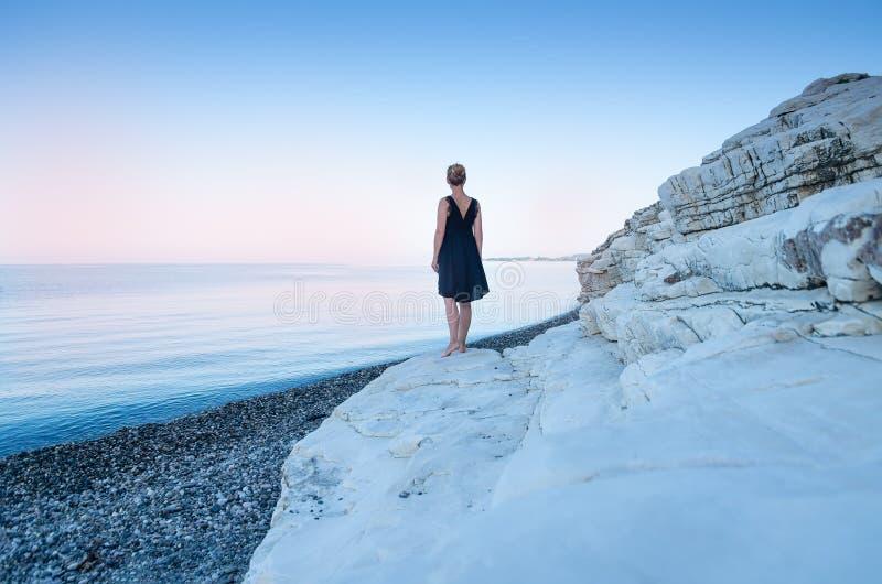 Een eenzaam meisje in een zwarte kleding bevindt zich op de kust Witte rotsen Het concept minimalism stock foto's