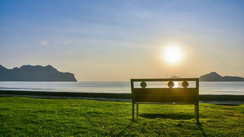 Een eenzame bank op groen gras dichtbij de kust bij Ao Manao royalty-vrije stock afbeeldingen