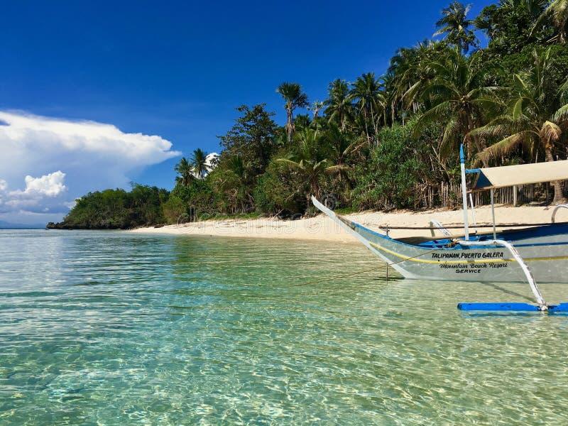 Een eenzame boot op het paradijs zandige strand, met duidelijk water, Phil stock fotografie