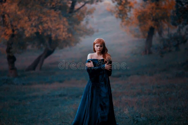 Een eenzame dame wandelt in de mist koesterend door de schouders van de koude Een gedeprimeerd roodharig meisje in een blauw stock foto