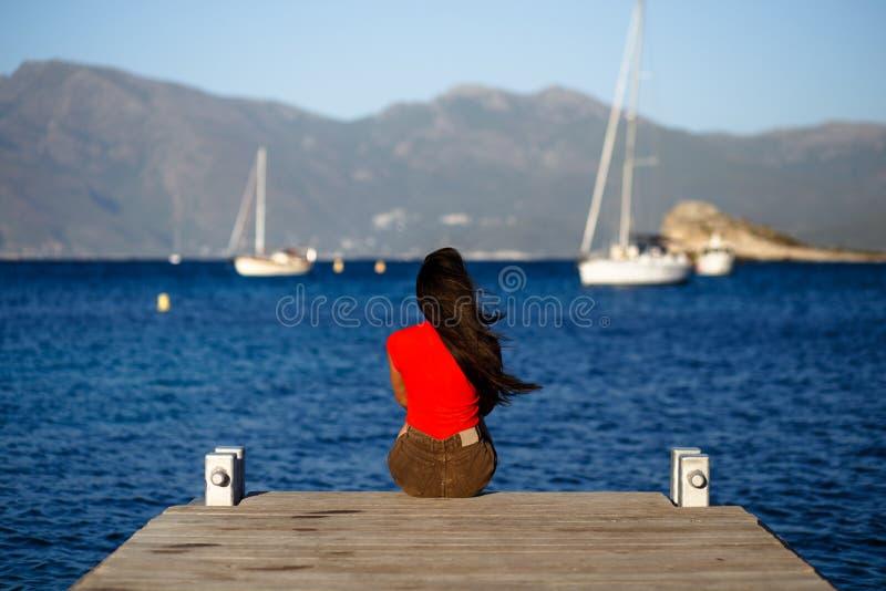 Een eenzame jonge donkerbruine vrouw in rode zitting met terug op houten pijler, het bewonderen zeegezicht van het eiland van Cor royalty-vrije stock fotografie