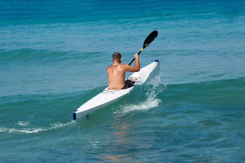 Een eenzame kayaker voer in het overzees in een kajak stock afbeelding