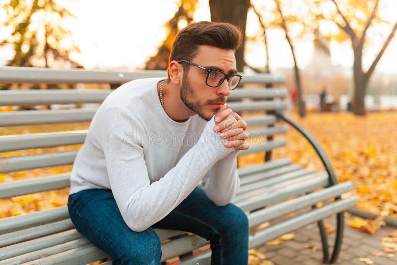 Een eenzame knappe mens zit droevig in het park op een bank De herfstseizoen, gele bladeren op achtergrond royalty-vrije stock foto's