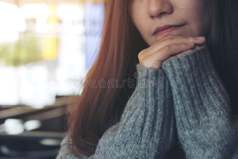 Een eenzame mooie Aziatische vrouwenzitting met kin die op haar handen alleen in moderne koffie rusten stock afbeelding