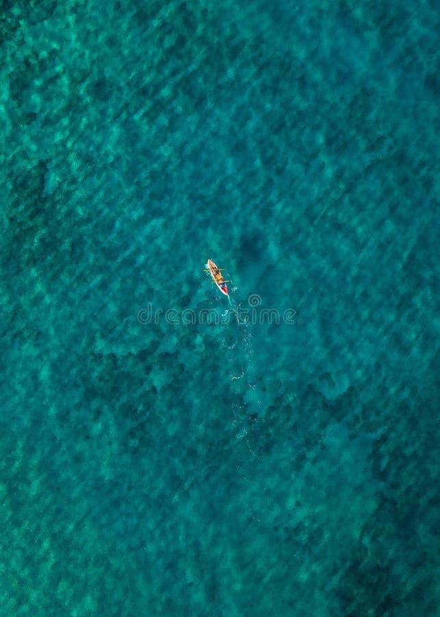 Een eenzame persoon die in het duidelijke wintertalingswater kayaking stock fotografie