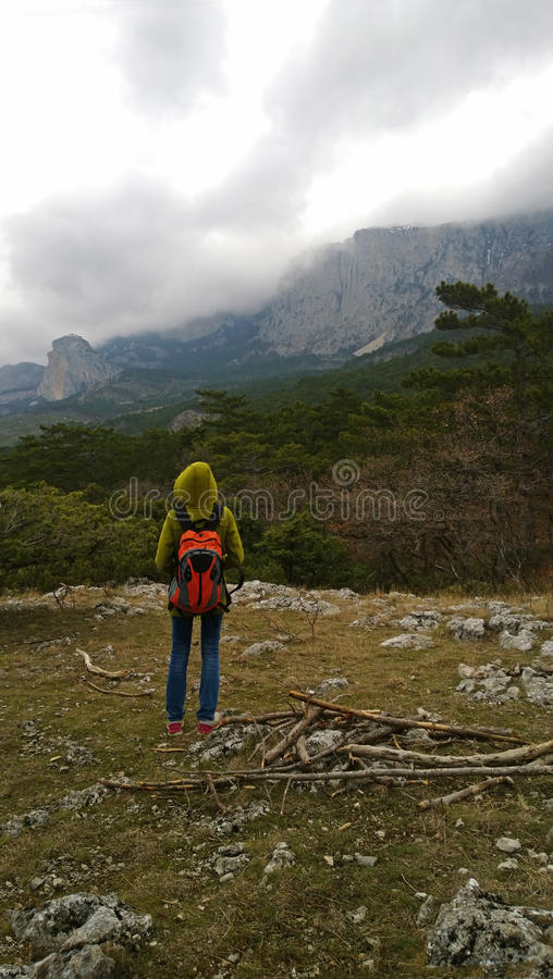 Een eenzame reiziger bevindt zich op de heuvel en bekijkt de bergen Bewolkt donker weer stock fotografie