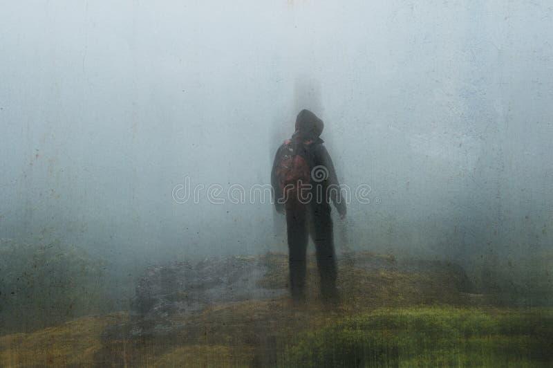Een eenzame spookachtige, met een kap wandelaar die neer van een heuvel, op een regenachtige, mistige dag kijken Met dark, grunge royalty-vrije stock afbeelding