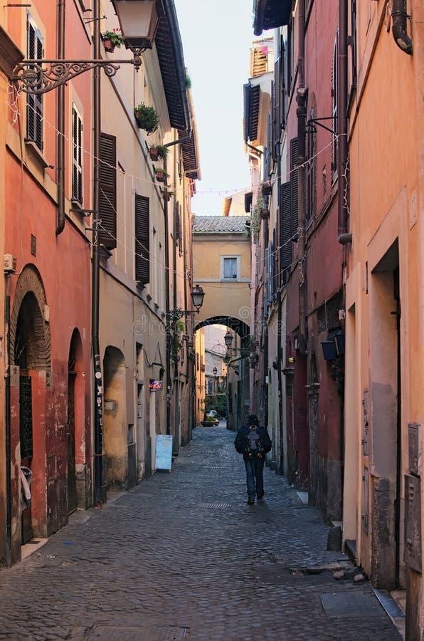 Een eenzame toerist met een rugzak loopt langs een smalle lange straat Mooie oude vensters in Rome (Italië) stock foto's