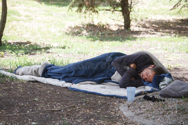 Een eenzame toerist verborg in een slaapzak en slaap ter plaatse in een stadspark, een dakloze persoonsslaap in de middag in stock foto