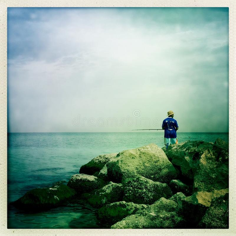 Een eenzame visser door de rotsen royalty-vrije stock foto's
