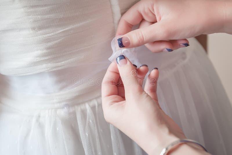 Een eerste bruidsmeisje helpt bij het binden van de het lintsjerp van de bruid op haar toga stock foto