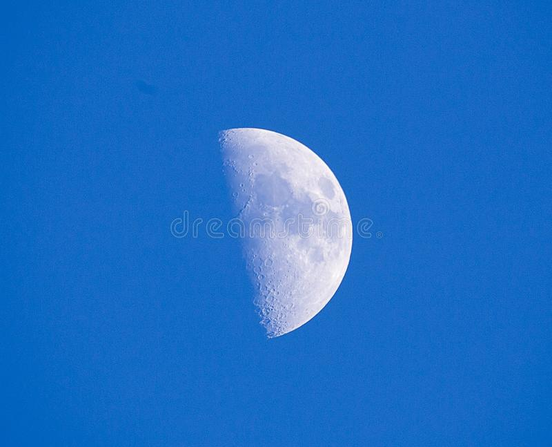 Een eerste kwartaalmaan tegen een blauwe hemel royalty-vrije stock foto