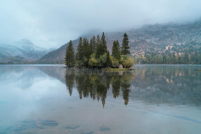 Een eiland met de eerste sneeuw van het jaar op een koud meer wordt berijpt dat stock fotografie