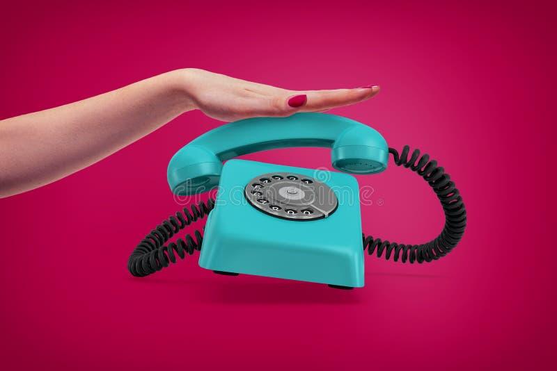 Een elegante vrouwelijke hand drukt een handvat van een retro blauwe roterende telefoon neer die omhoog belt en bijna springt stock fotografie