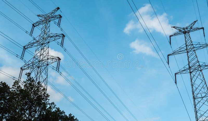 Een elektriciteitspylonen met hoog voltage tegen blauwe hemel met wolken bij zonnige dag Torens de met hoog voltage van de machts stock afbeelding