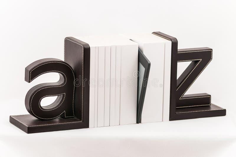 Een elektronische boeklezer onder gedrukte witte dekkingsboeken stock afbeelding