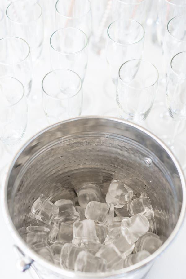 Een emmer van het metaalijs met hoogtepunt van verpletterd ijs en roestvrije lepel voor dessert op lijst in hotel royalty-vrije stock afbeeldingen