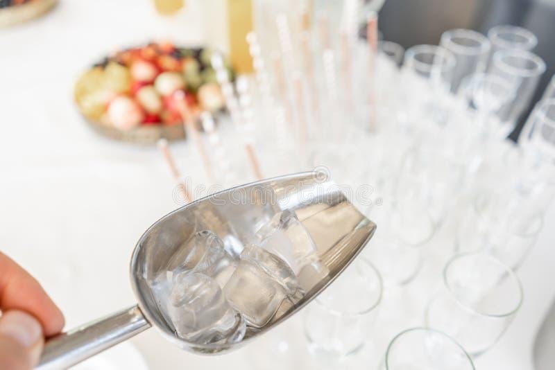 Een emmer van het metaalijs met hoogtepunt van verpletterd ijs en roestvrije lepel voor dessert op lijst in hotel royalty-vrije stock fotografie