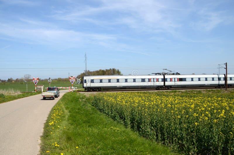 Een EMOEtrein gaat een spoorwegovergang met een het wachten auto over royalty-vrije stock afbeeldingen