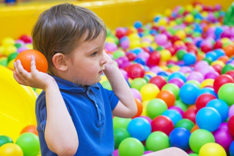 Een emotioneel gezicht van het glimlachen baby het spelen in de ballenpool Het gelukkige jong geitje spelen met gekleurde ballen  stock afbeeldingen
