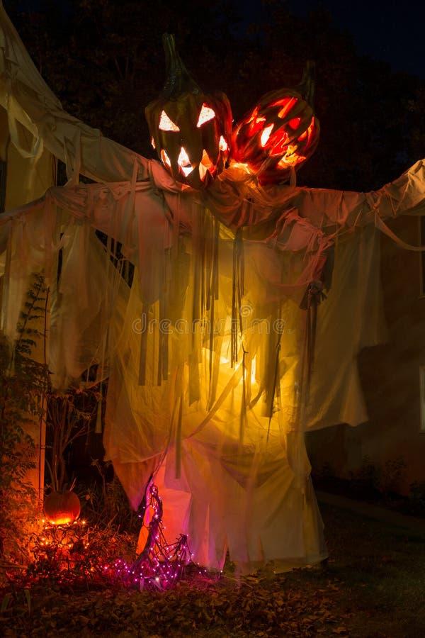 Een enge vertoning van twee leidde pompoenspook bij nacht met gele verlichting die aan dit Halloween kijkend vertoning toevoegt royalty-vrije stock foto