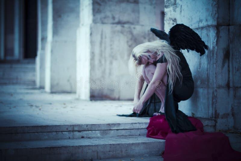 een engel in de stad, mooi blonde met lang haar kleedde zich binnen stock afbeelding