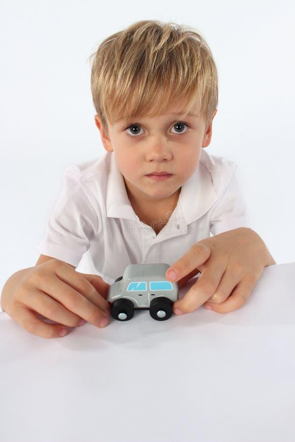 Een engelachtige kijkende kindjongen die zijn favoriet eenvoudig houten autostuk speelgoed tonen royalty-vrije stock fotografie