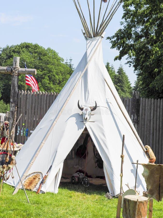 Een enig, solitair tipi op een gebied De tipi worden gebruikt in vele de zomerkampen als schuilplaats voor de kampeerauto's stock foto's