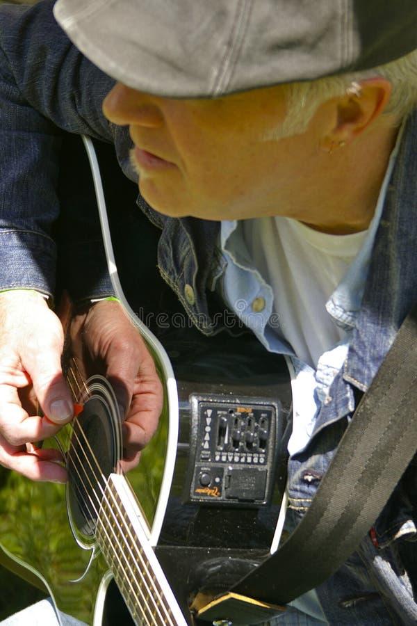 Een enkel mens en zijn gitaar stock foto's